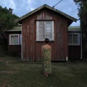 Beate Kuhn - Foto Frau vor einem Holzhaus